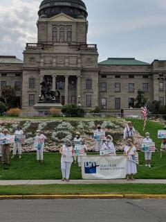 LWV members dressed in white holding ERA posters outside Montana Capitol