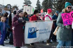image of three women holding League of Women Voters banner and marching