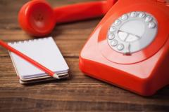 Red phone on a desk with a notepad