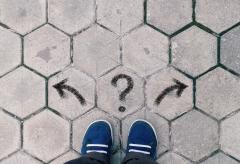 Person looking at the their feet trying to decide which way to go with a right arrow, left arrow and question mark in the middle