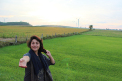 Girl standing in a meadow with her hand outstretched
