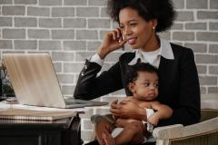 Woman holding an infant while she is in front of the computer and on the phone working