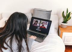Young woman video chatting on laptop at home, laying on bed at a Virtual meeting,