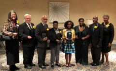 Eight individuals holding award plaques