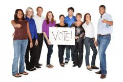 """diverse group holds a sign that says """"Vote"""""""