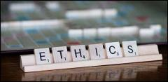 A Scrabble tray holding tiles that spell the word ETHICS