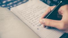 Person writing a list in a journal