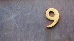 Brass number nine on slate background