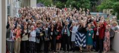 An image of at least one hundred delegates to the LWVC 2019 convention, who are wearing convention badges and waving at the camera.