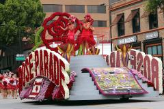 Photo of a Rose Parade float, on which stand three women in red dresses holding microphones.