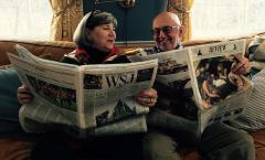 Journalists Naomi Shalit and John Christie seated with newspapers
