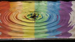 time lapse photography of water ripple with pride colors