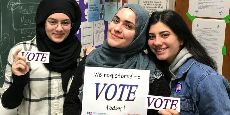 "High school students pose with ""WE REGISTERED TO VOTE TODAY"" and ""VOTE"" signs"