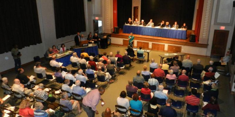 Image looking down on an theater filled with people in the audience, and a line of candidates sitting on the stage
