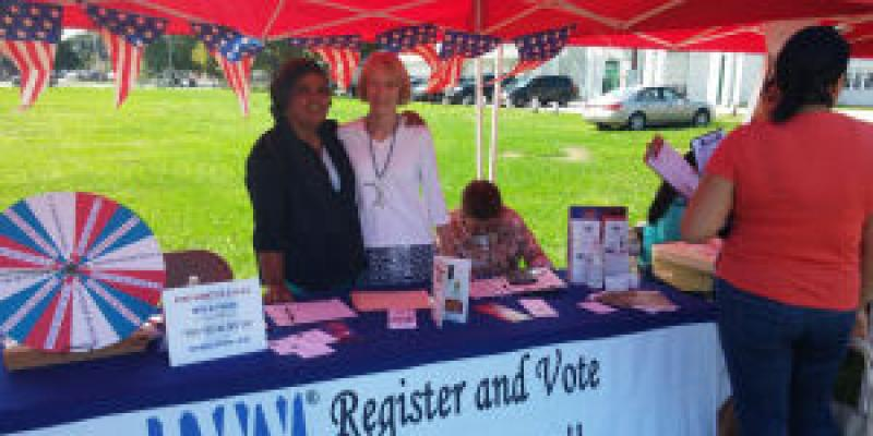 League members standing behind a voter registration table, outside, under a red tent