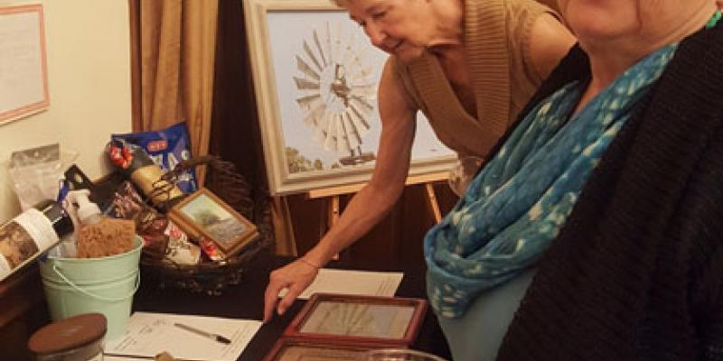 Two LWV Hays County members check bid sheets during silent auction