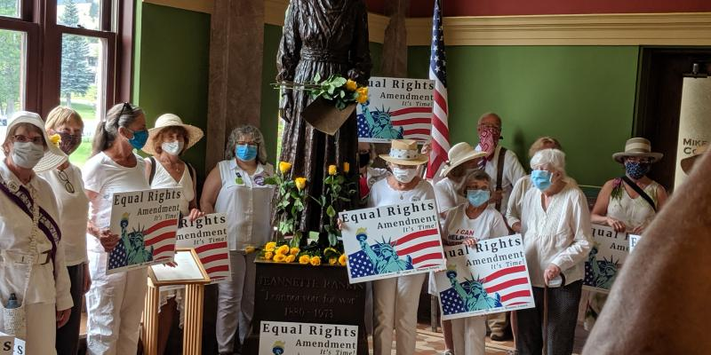 photo of people in white around statue of Jeannette Rankin in Montana Capitol
