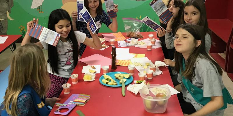 photo--Girl Scouts enjoy snack time after a program on the League