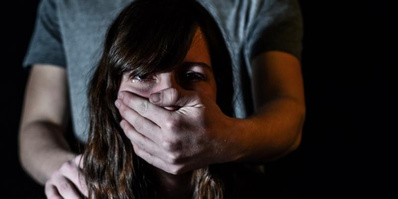 A picture of a man covering a frightened girls mouth with his hands (human trafficking)