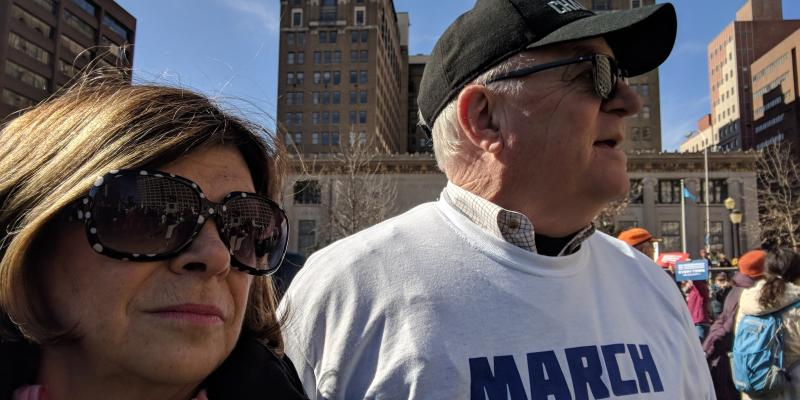 "Woman and man standing outdoors in city, man wearing ""March for our..."" t-shirt"