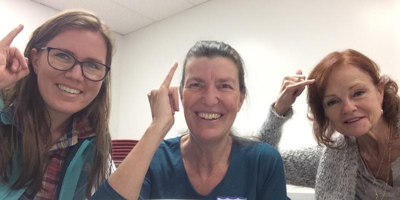 "Three women, making the ASL ""idea"" sign with their pinkie fingers"