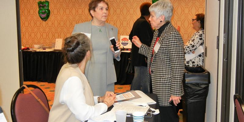Three League members in conversation attending the 2019 LWVLA convention. One seated and two standing.