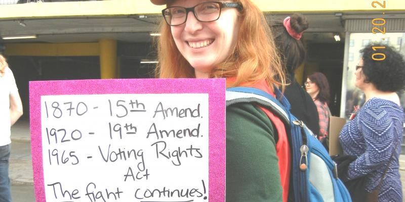 Leager in hat carrying a sign listing the voting rights acts in 2018 New Orleans Women's March