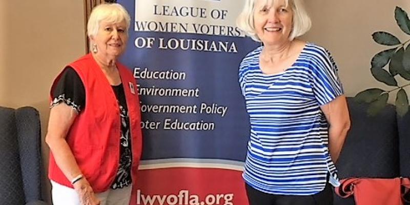 Two women in front of red, white and blue LWVLA banner