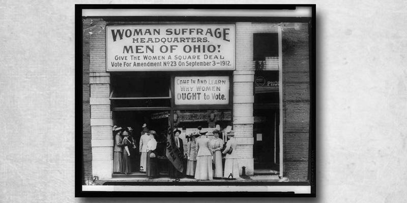 Photo from 1920 of women standing in front of a building, which has a sign that says Woman Suffrage headquarters