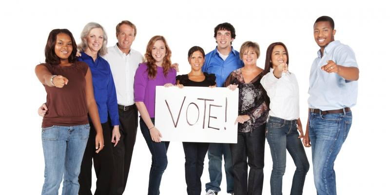 "diverse group holds a sign that says ""Vote"""