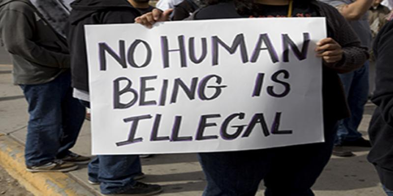Sign from a march reads No Human Being is Illegal