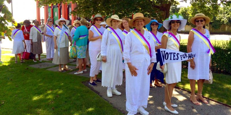 LWVRI members dressed as suffragettes, holding VOTES FOR WOMEN signs