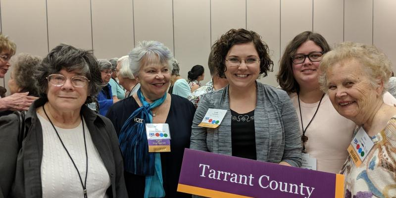 Five LWV Tarrant County (TX) members pose for photo at LWVTX Convention 2018, with Tarrant County sign