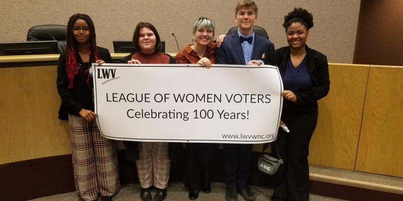 "People holding up sign that reads: ""LEAGUE OF WOMEN  VOTERS 