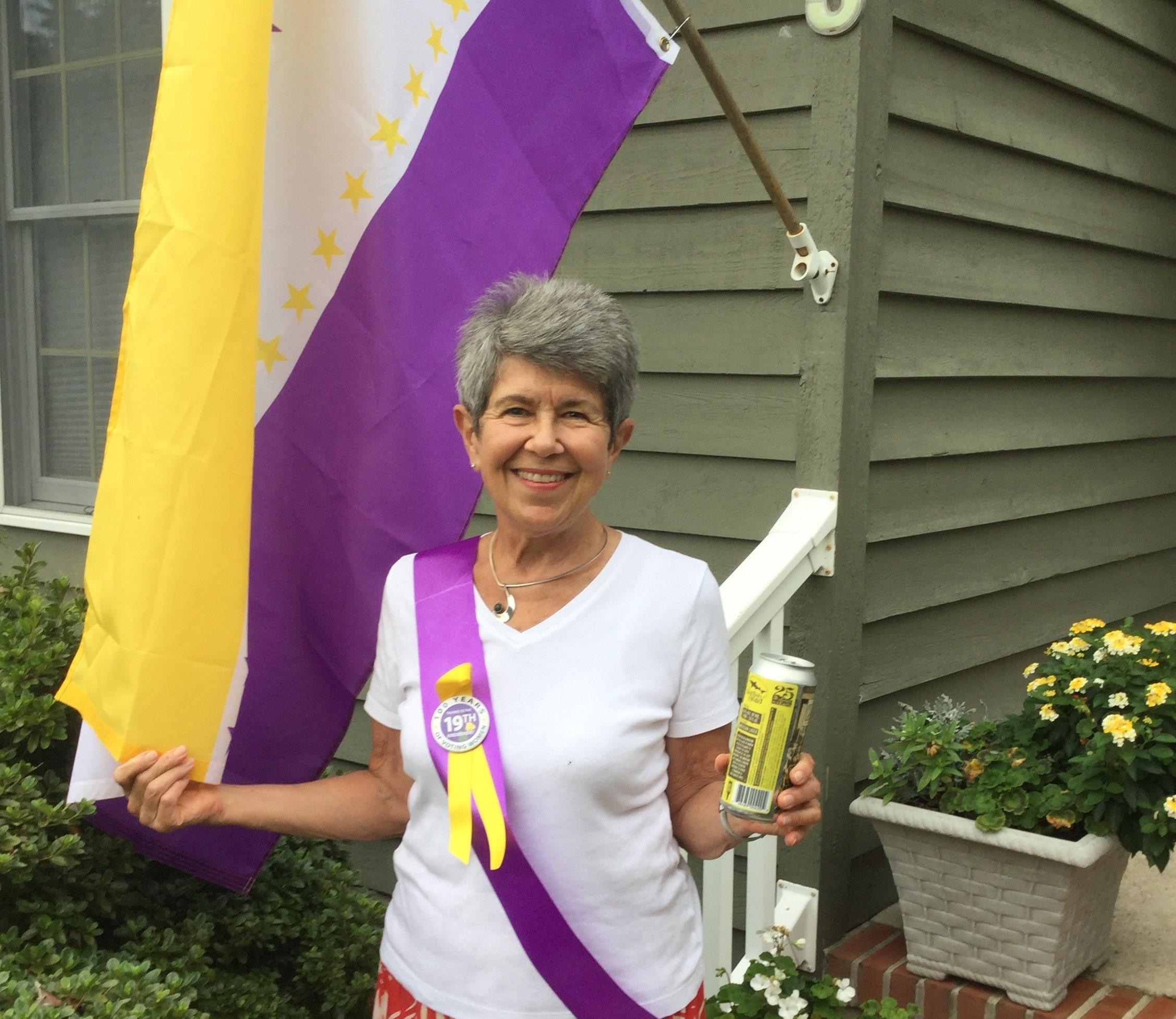 Sue Claire Harper flies 19th Amendment flag while holding a can of Centennial Suds