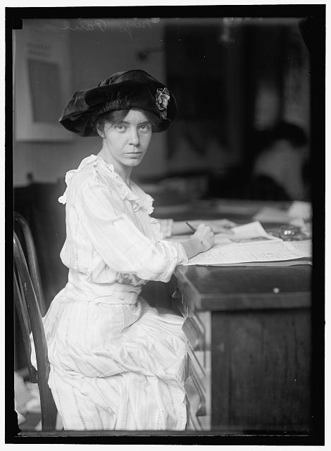Vintage photo - Woman with dark hair and hat sits at desk and looks to the camera