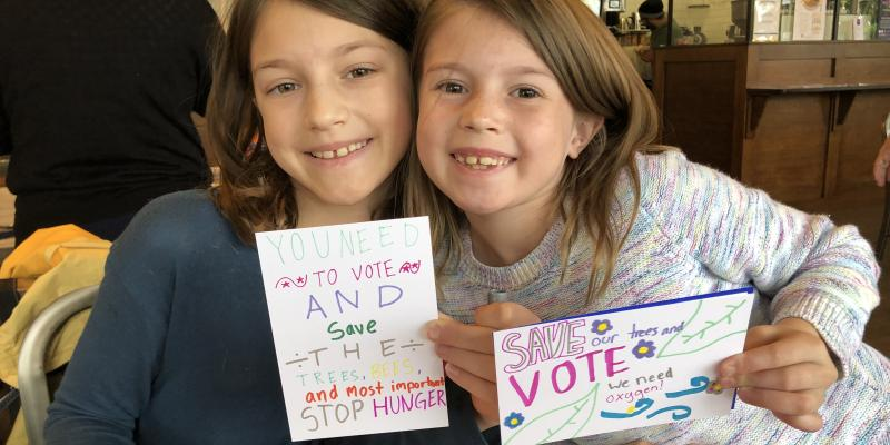 "children with ""vote"" postcards"